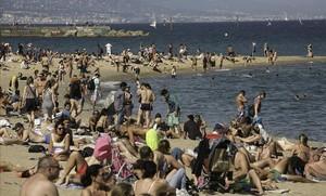 Aspecto de la playa de la Barceloneta conmucha gente disfrutando de la temperatura veraniega.