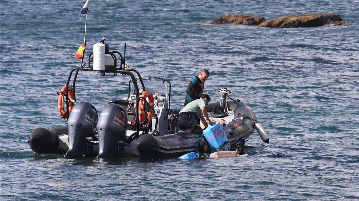 Agentes de la Guardia Civil recogen del agua fardos de hachís en la zona de San García, en Algeciras (Cádiz).
