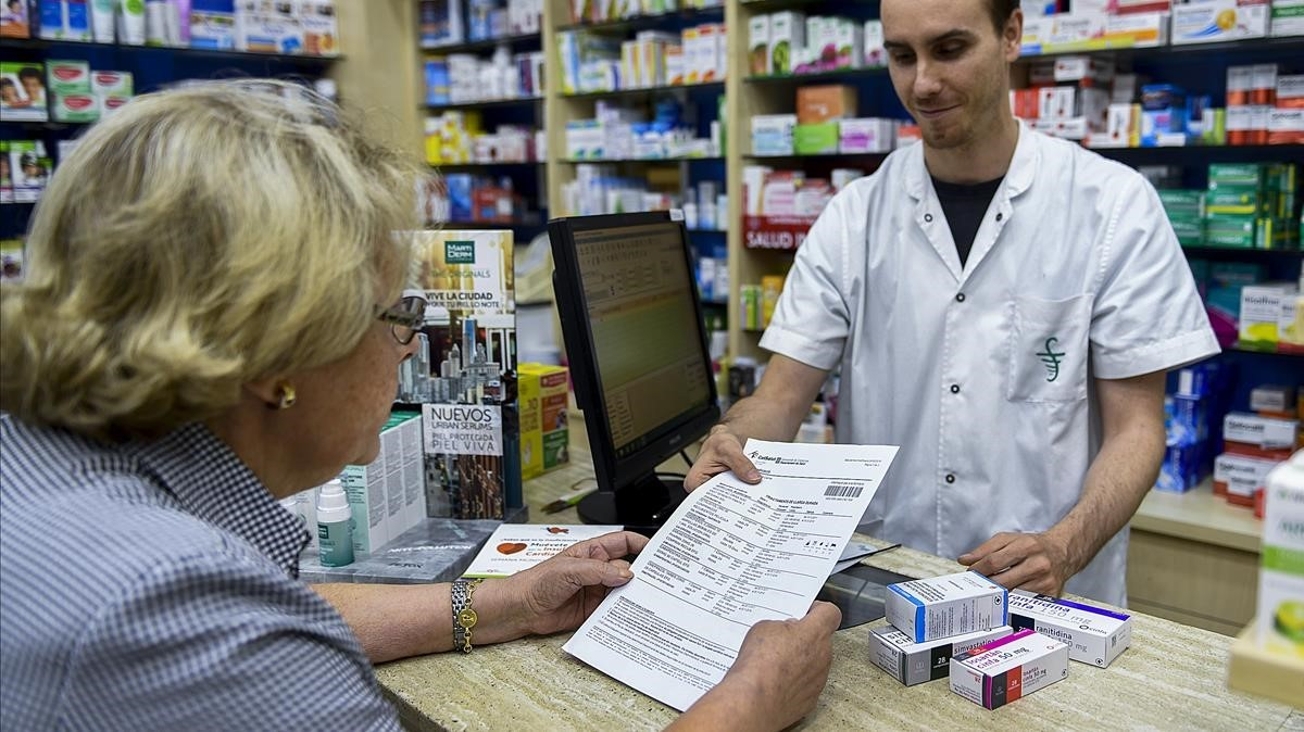 Una paciente muestra su receta en la farmacia para cambiar por la mediacion correspondiente, este viernes en Barcelona.