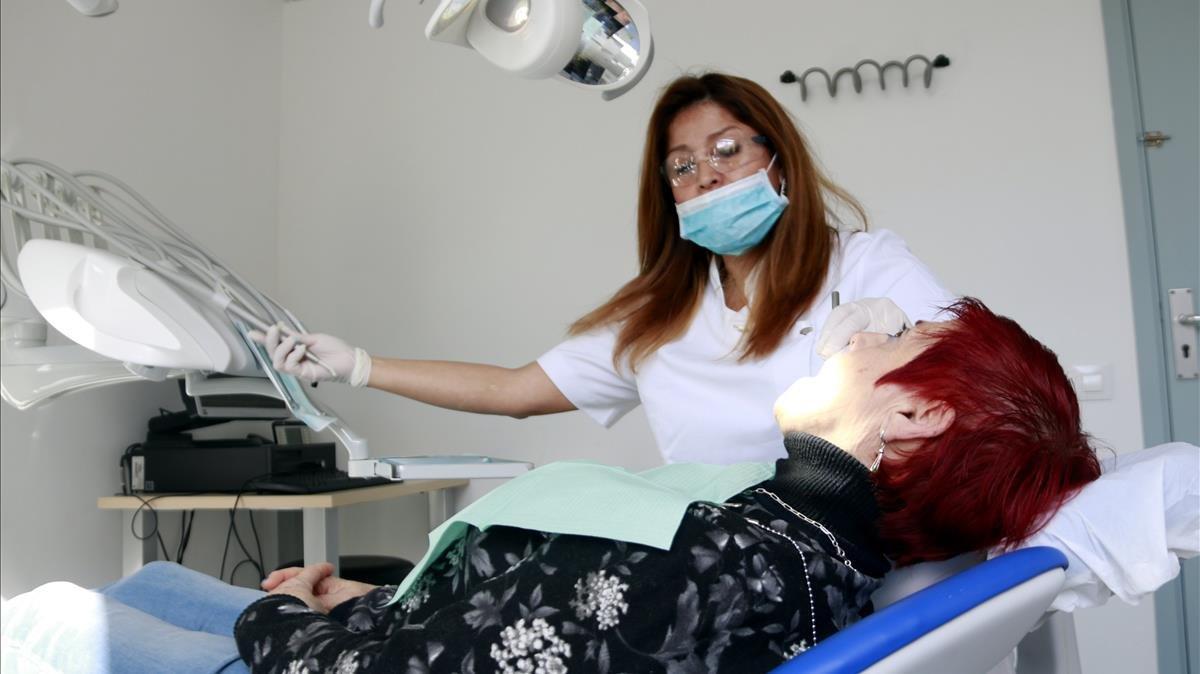 Una dentista atiende a un paciente en la nueva consulta municipal de odontología de la calle de Viladonat, ayer.