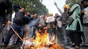 Miembros de la comunidad sij queman fotos del político condenado.