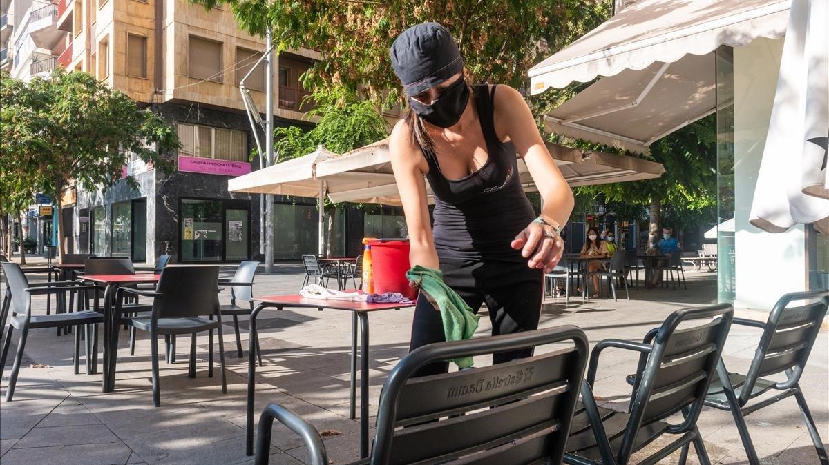 Una trabajadora desinfecta una terraza para preparar la reapertura del local tras los 15 días de cierre impuestos en Lleida.