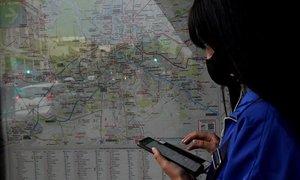 Una usuaria consulta el trayecto del autobús en una parada de Punte de Vallecas.