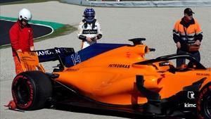 Alonso observa el coche tras una problema mecánico que le ha dejado fuera