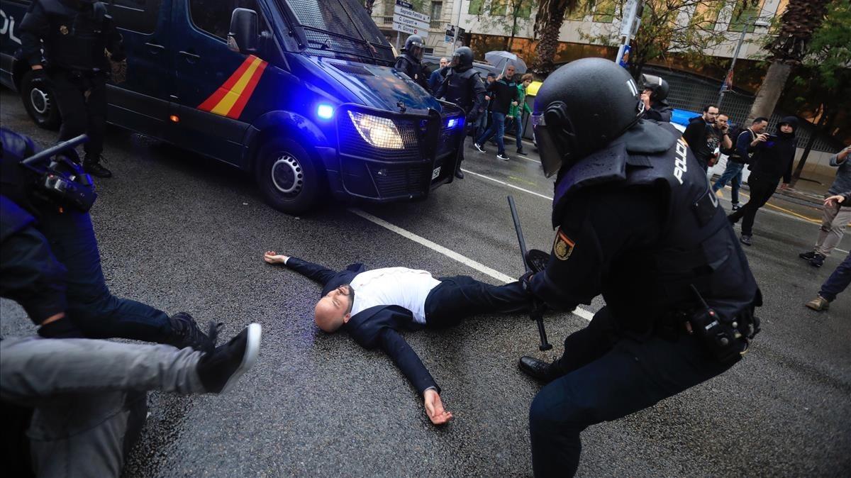 Un agente retira de la pierna a un hombre que impidía el paso de la Policía Nacional tras la carga en la escuela Ramon Llull.