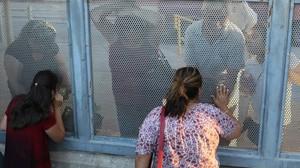 Ana Pineda (a la derecha) habla con sus familiares desde el lado estadounidense de la frontera de Nogales.