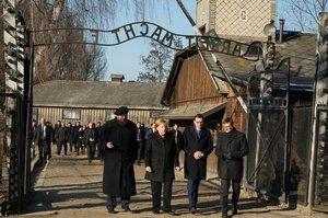 Angela Merkel cruza la puerta de entrada del campo de concentración de Auschwitz, bajo el siniestro cartel 'El trabajo os hará libres'.