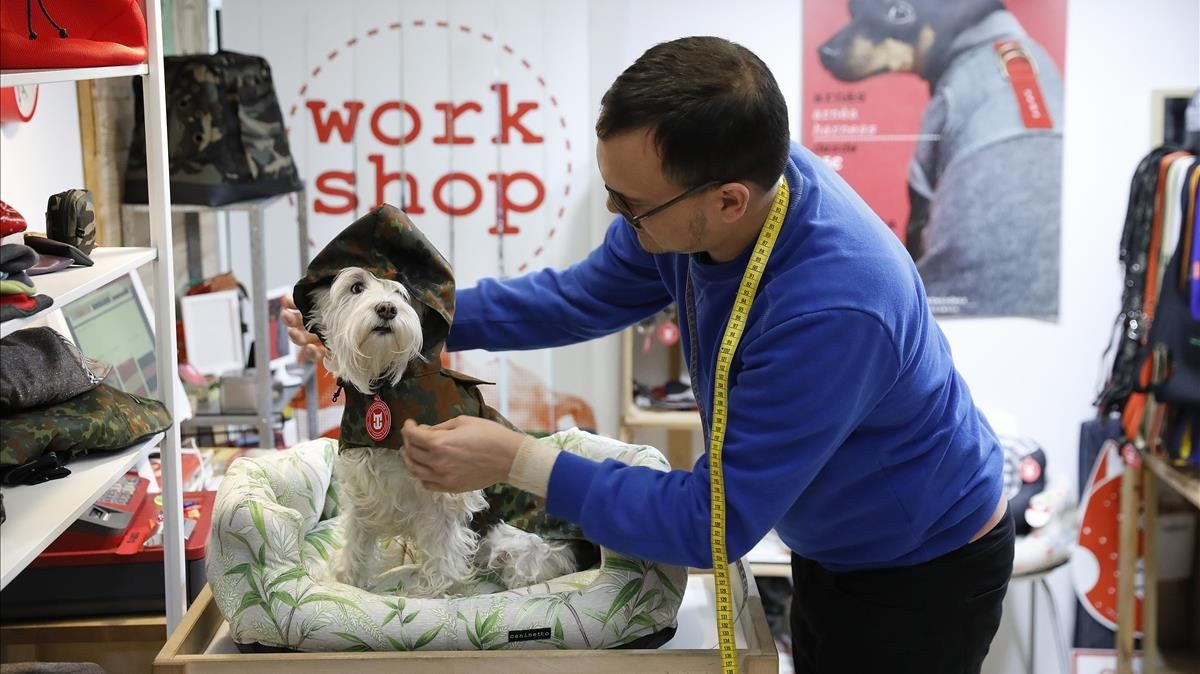 Edgar pruebaun chubasquero de camuflaje aNeima, una de las clientas de Caninetto, en el probador de la tienda: un cambiador de bebés.