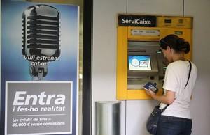 Una mujer operando en un cajero automático en Barcelona.