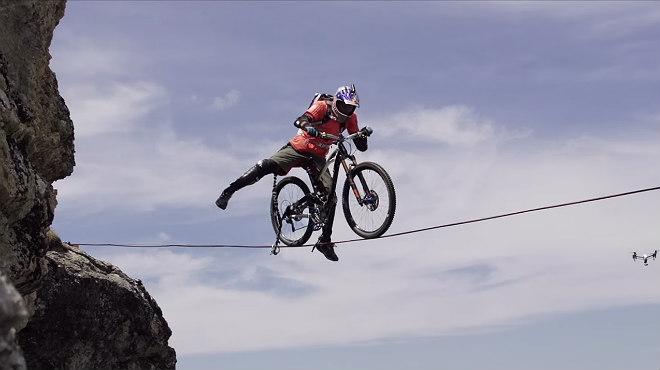 El campeón mundial de trial, Kenny Belaey, cruza una montaña por una cuerda floja.