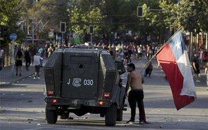 Un manifestante se enfrenta a un vehículo militar durante las protestas en Chile.