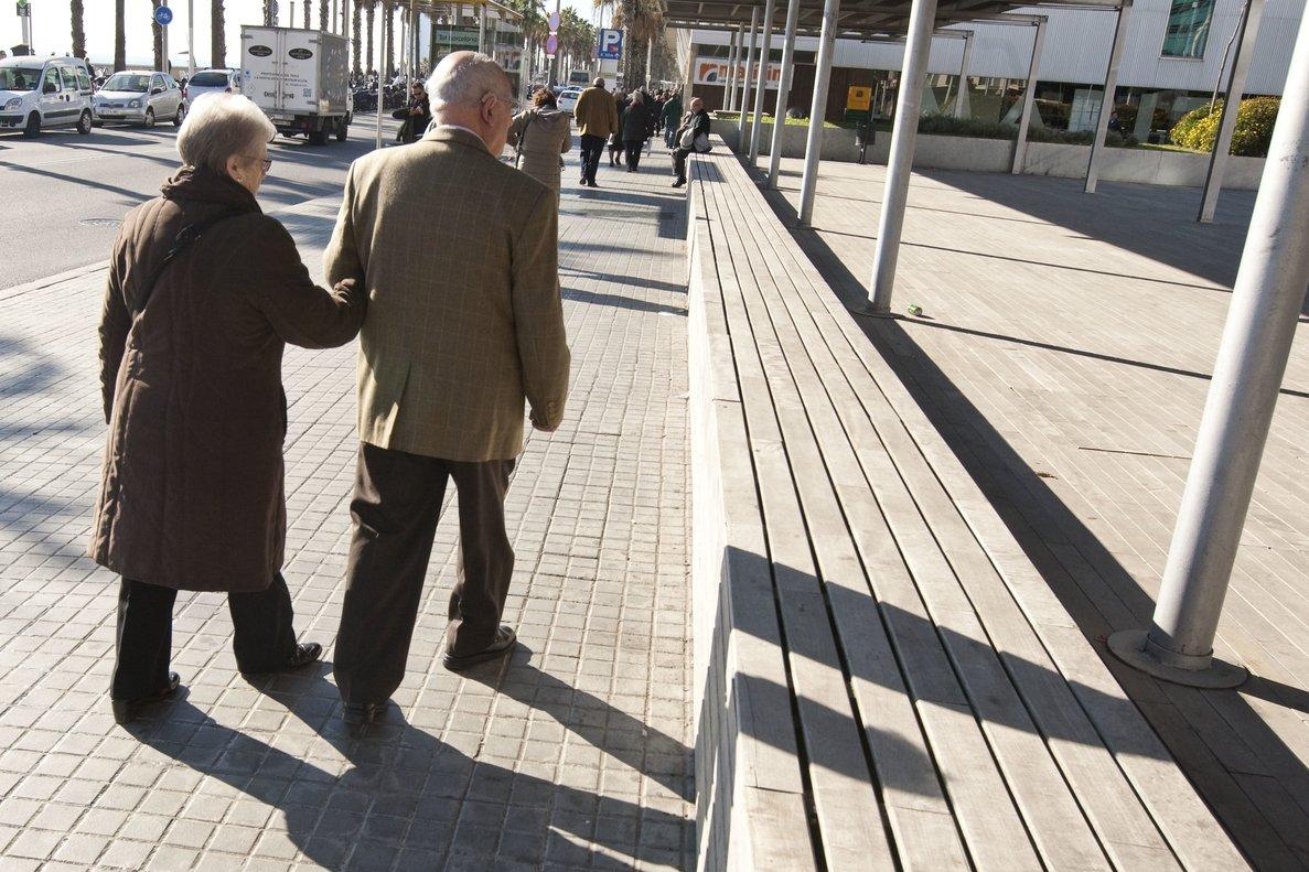 Dos ancianos caminan por una calle.