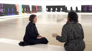 Dos mujeres conversan ante algunos de los 102 lienzos de la monumental 'Sombras' de Andy Warhol expuesta en el Guggenheim de Bilbao.