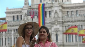 Dos turistas se hacen un selfie frente al Ayuntamiento de Madrid, que luce la bandera del arcoiris en homenaje al World Pride 2017.