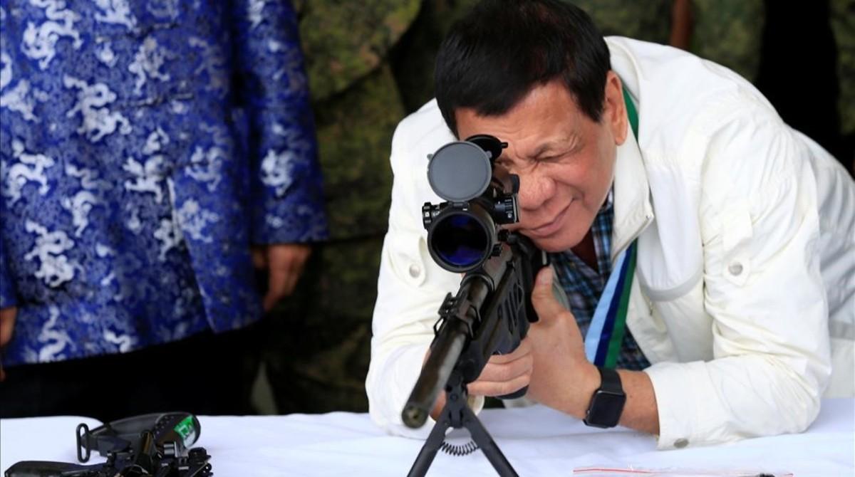 Duterte comprueba la mirilla de un rifle, hace unos días.