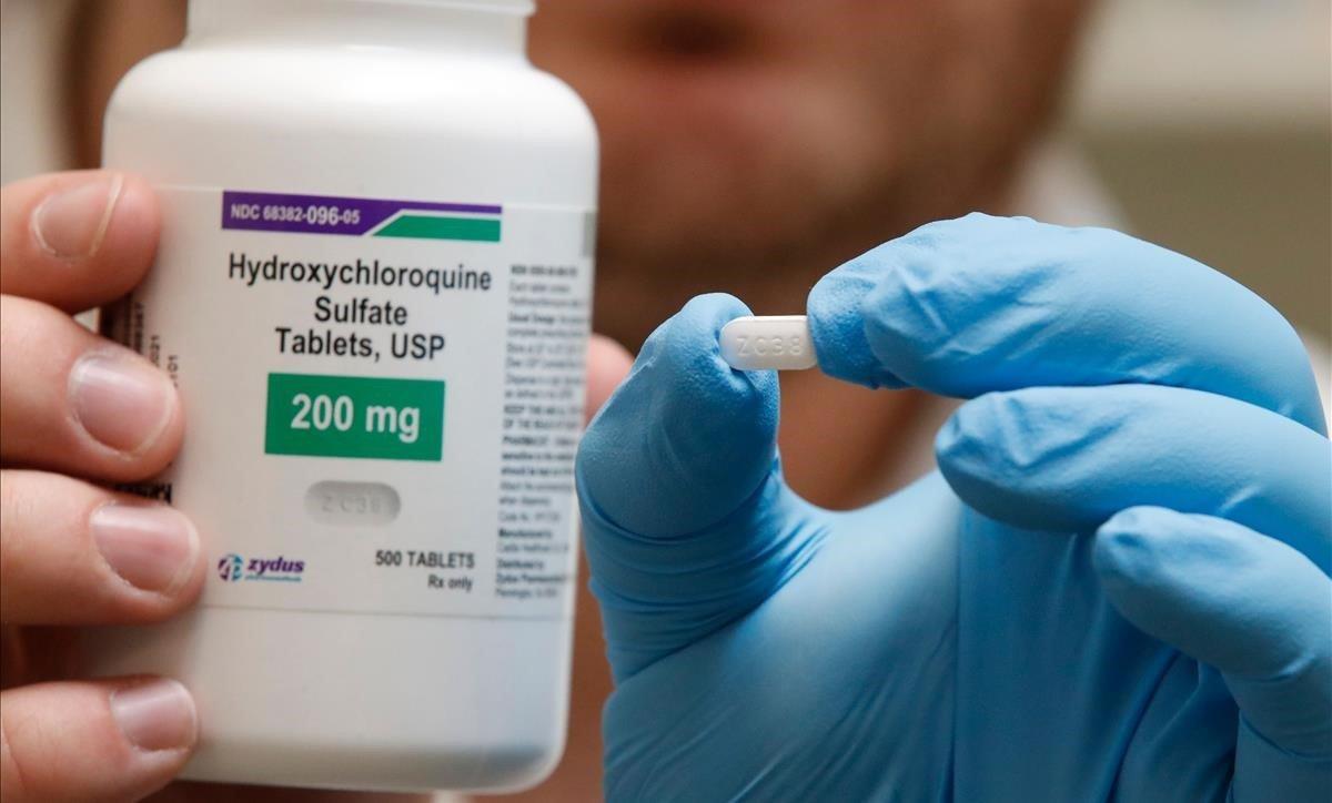 Un farmacéutico sostiene una píldora de hidroxicloroquina.