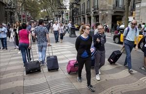Turistas con maletas por las calles de Barcelona.