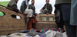 Un grupo de afganos trasladan los cuerpos de las 13 víctimas civiles asesinadas en Kunduz.