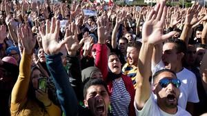 Jóvenes con los brazos en alto durante la masiva manifestación en Alhucemas, en el norte de Marruecos, el 18 de mayo.