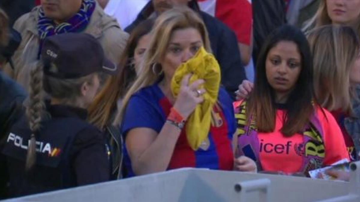 Una mujer besa una camiseta amarilla antes de arrojarla a uncontenedor en la final de Copa.