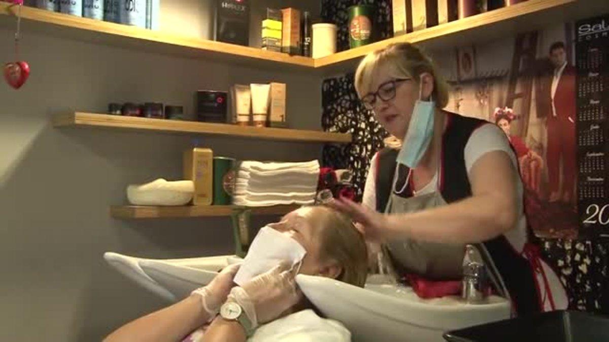 La propietaria de la peluquería 'Total Look',de Ripollet, atiende a una clienta.