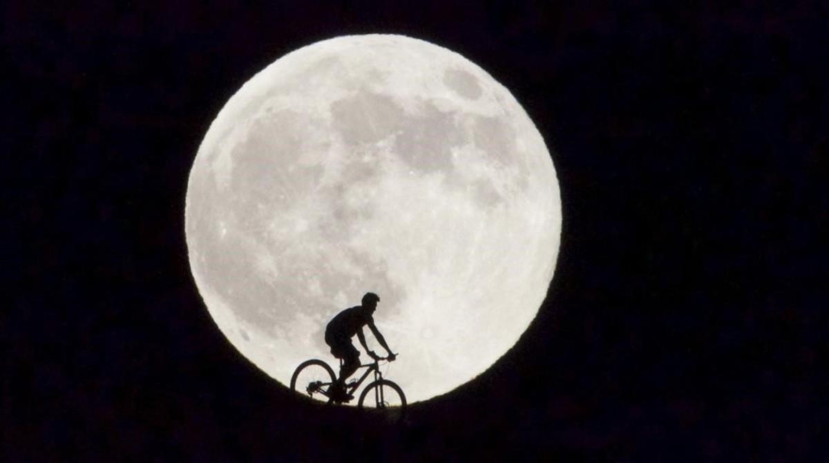 Un ciclista pasa delante de la Luna llena que en la isla canaria de Fuerteventura.