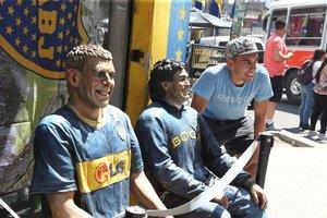 Un aficionado de Boca se fotografía junto a una imagen de Maradona y otra de Palermo, la semana pasada en Buenos Aires.