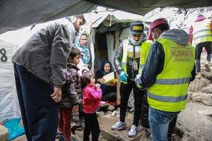Miembros de la oenegé Team Humanity entregan mascarillas en un campo de refugiados de Lesbos.