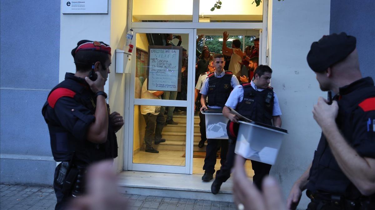 Mossos d'esquadra retiran urnas de un centro de votación, el 1 de octubre del 2017.