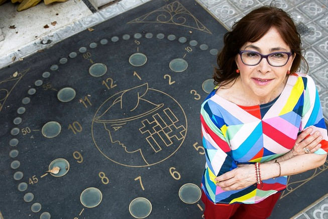 La periodista Rosa Badia, sobre el reloj luminoso de Via Laietana, situado a la altura del número 69.