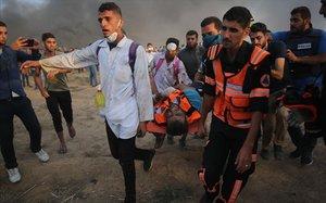 Personal sanitariopalestino trasladan a un manifestante herido durante los enfrentamientos con las fuerzas israelís al este de la ciudad de Gaza.