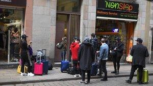 Turistas aguardan en la entrada de su alojamiento en la calle Ferran de Barcelona.
