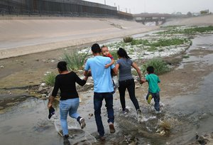 CIUDAD JUAREZ, MEXICO - MAY 20: Migrants hold hands as they cross the border between the U.S. and Mexico at the Rio Grande river, on their way to enter El Paso, Texas, on May 20, 2019 as taken from Ciudad Juarez, Mexico. The location is in an area where migrants frequently turn themselves in and ask for asylum in the U.S. after crossing the border. Approximately 1,000 migrants per day are being released by authorities in the El Paso sector of the U.S.-Mexico border amidst a surge in asylum seekers arriving at the Southern border. Mario Tama/Getty Images/AFP
