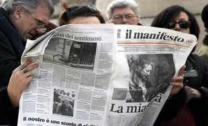 Una mujer leyendo el periódico italiano Il Manifesto.