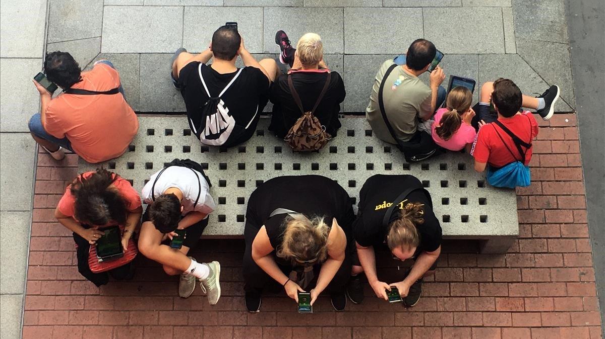 Varias personas miran su móvil.