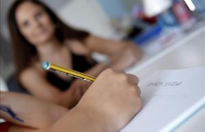 Un niño hace los deberes ante la atenta mirada de su madre.
