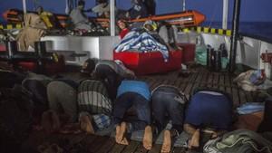 Algunos inmigrantes que viajan en el Open Arms rezan en cubierta en su viaje hacia el puerto de Barcelona.