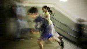 Dos niños corren a la entrada del colegio en Barcelona.
