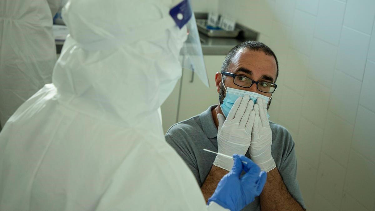 Un profesional sanitario se dispone a hacer una prueba PCR a un hombre.