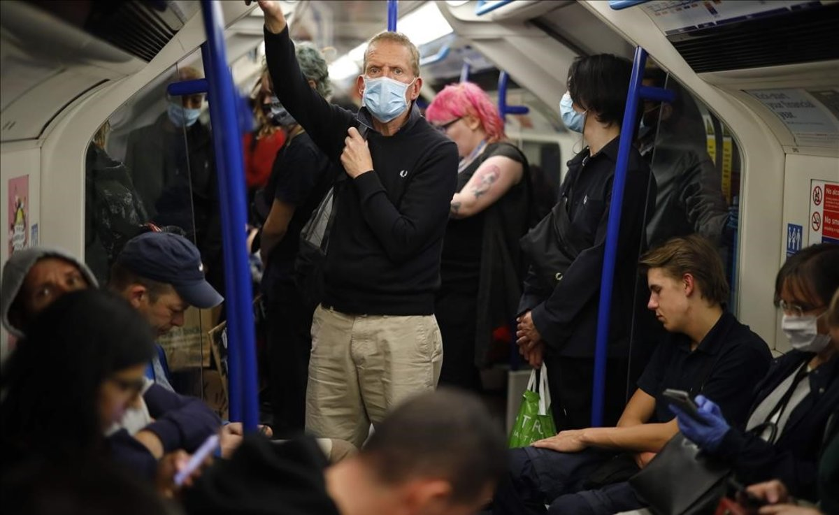 Pasajeros con mascarilla en el metro de Londres.