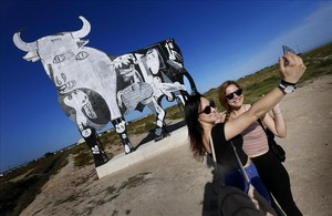 Turistas se acercan a fotografiarse y observar el toro de Osborne que ha aparecido pintado con el escenas del Guernica de Picasso en Santa Pola, Alicante.