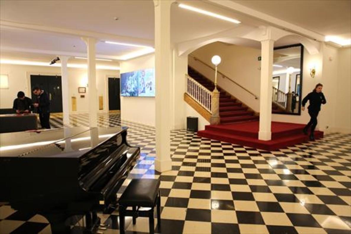 Vestíbulo del Teatre Romea, en el que hay un piano y una imponente escalera.
