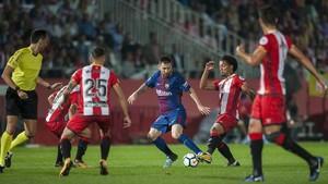 Messi trata de superar a sus rivales del Girona