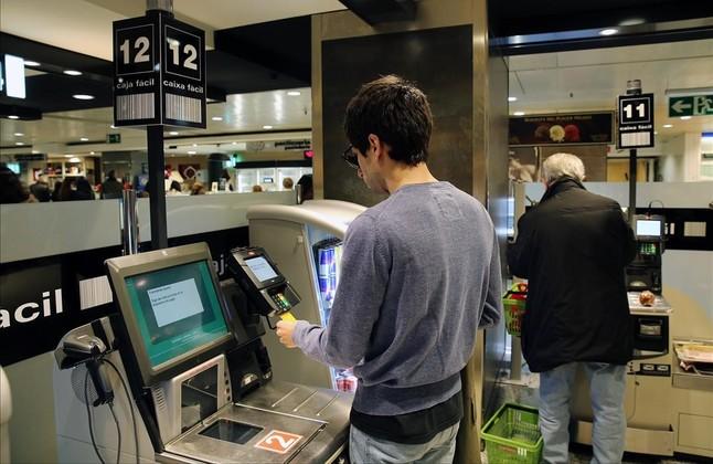 Un clientechequea sus productos en el supermercado de El Corte Inglés de plaza de Catalunya, el viernes.