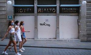 Jóvenes con mascarilla pasan por delante de la entrada de un hotel cerrado, en Barcelona.