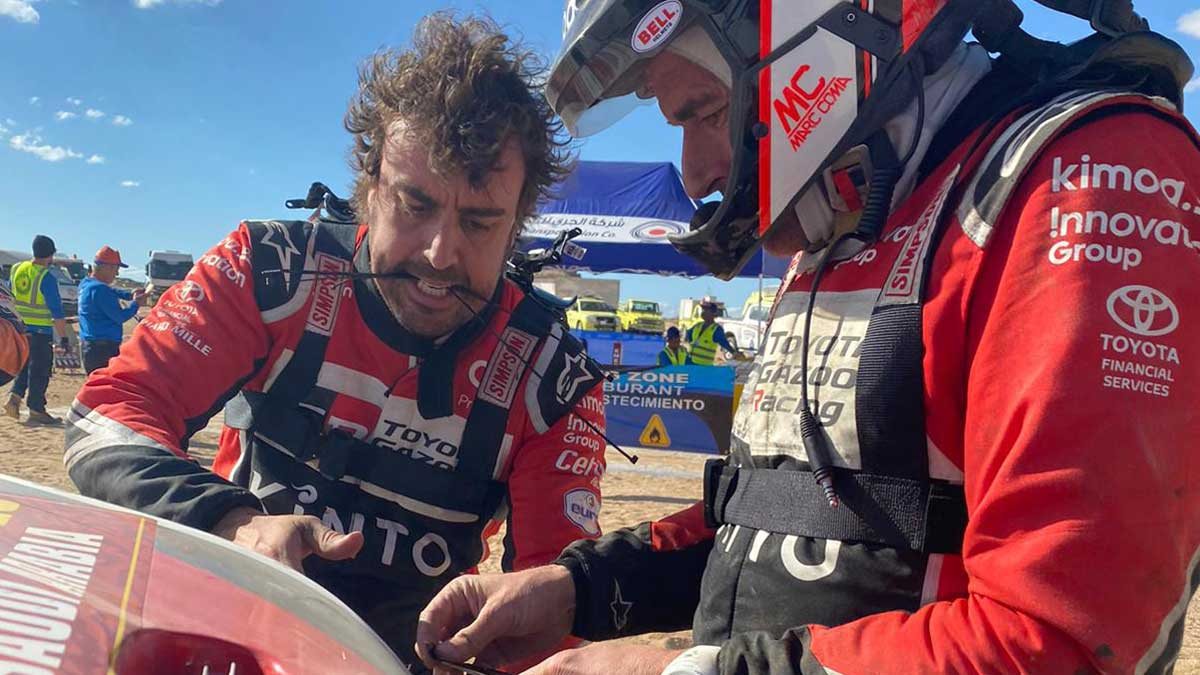 Fernando Alonso tras reparar su coche: Quiero vivir el Dakar hasta el final. En la imagen, el piloto, junto a Marc Coma, mientras trataba de arreglar su vehículo.