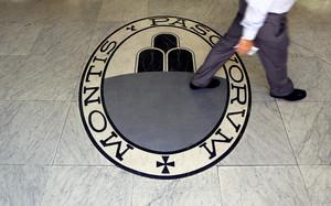 Un hombre camina sobre el logo del banco Monte Dei Paschi Di Siena en Roma.