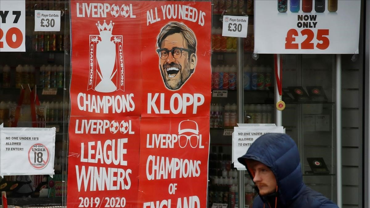 Un hombre pasa ante pancartas del Liverpool como campeón de la Premier.