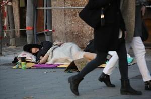 Un hombre sin hogar duerme y pide ayuda a la vez en una acera del paseo de Gràcia, el pasado noviembre.