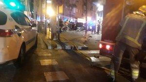 Imagen de la terraza del bar donde ha tenido lugar el accidente, con el vehículo al fondo, en la calle Mare de Déu del Remei, en Girona.